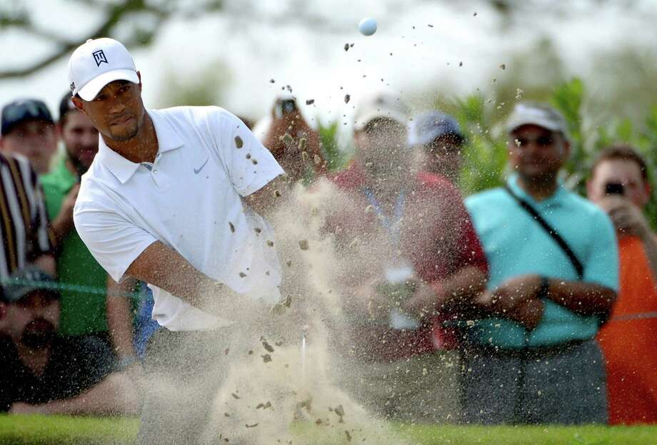Tiger Woods hits out of a bunker onto the 14th green during the third round of the Arnold Palmer Invitational in Orlando, Fla. Woods leads by two shots. Photo: Phelan M. Ebenhack / Associated Press