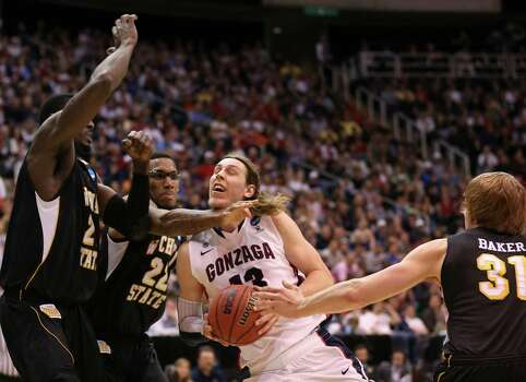 SALT LAKE CITY, UT - MARCH 23:  Kelly Olynyk #13 of the Gonzaga Bulldogs drives to the basket against Ehimen Orukpe #21 and Carl Hall #22 of the Wichita State Shockers in the first half during the third round of the 2013 NCAA Men's Basketball Tournament at EnergySolutions Arena on March 23, 2013 in Salt Lake City, Utah. Photo: Streeter Lecka, Getty Images / 2013 Getty Images