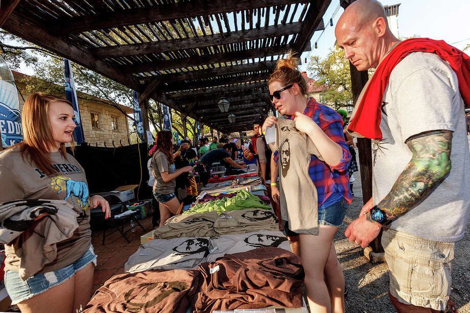 Shelby Reckendorf (left) helps Jim Eckenrode (right) and his wife Becky pick out concert t-shirts during the first annual Maverick Music Festival at  La Villita's Maverick Plaza on Saturday, March 23, 2013.  Austin's Gary Clark, Jr. and The Toadies from Fort Worth headlined the event that included Girl in a Coma, Arum Rae and  Henry + the Invisibles among others.  MARVIN PFEIFFER/ mpfeiffer@express-news.net Photo: MARVIN PFEIFFER, Express-News / Express-News 2013