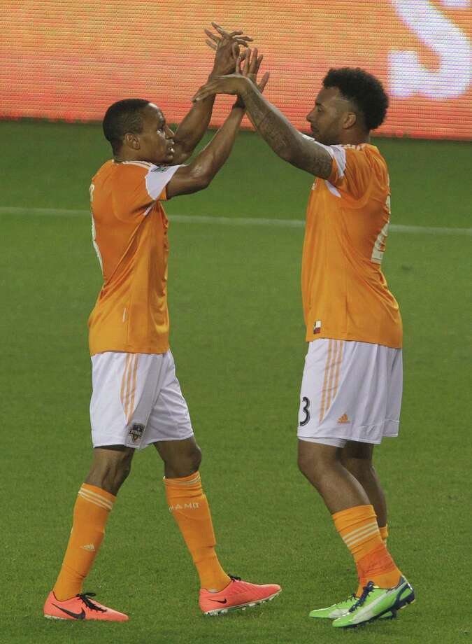 Ricardo Clark and Giles Barnes celebrate after Barnes scored a goal against the Vancouver Whitecaps. Photo: James Nielsen, Houston Chronicle / © 2013 Houston Chronicle