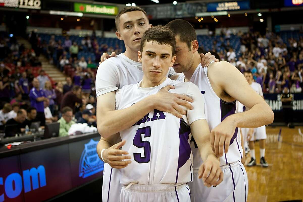 College Park's Mikey Eggleton, center, is consoled by teammates Tommy Acton and Peter Schoeman after losing to Redondo Union at the CIF State Basketball Championships March 23, 2013 in Sacramento, California.