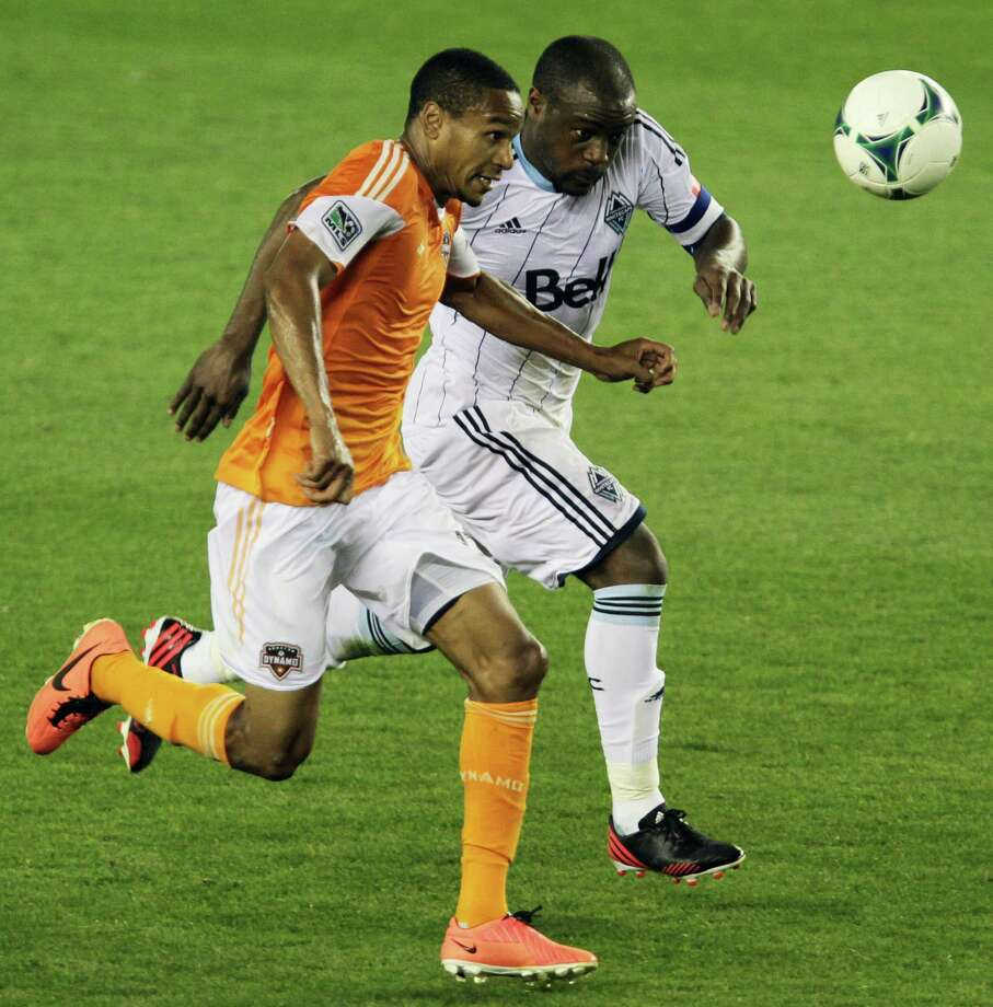 The Houston Dynamo's Ricardo Clark left, and Vancouver Whitecaps Nigel Reo-Coker chase the ball during the second half of MLS game action at BBVA Compass Stadium Saturday, March 23, 2013, in Houston . Photo: James Nielsen, Houston Chronicle / © 2013 Houston Chronicle
