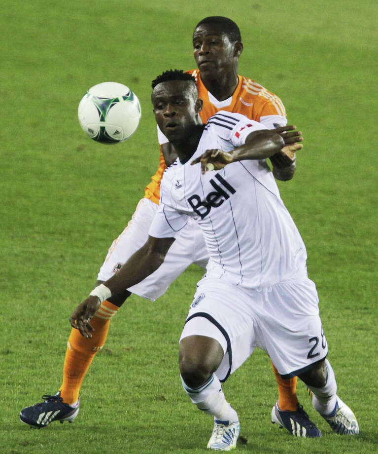 Dynamo defender Kofi Sarkodie and the Gershon Koffie fight for the ball. Photo: James Nielsen, Houston Chronicle / © 2013 Houston Chronicle