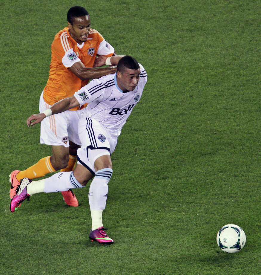 Ricardo Clark and the Whitecaps Erik Hurtado chase the ball. Photo: James Nielsen, Houston Chronicle / © 2013 Houston Chronicle