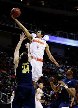 SAN JOSE, CA - MARCH 23:  Michael Carter-Williams #1 of the Syracuse Orange goes up over Robert Thurman #34 of the California Golden Bears in the first half during the third round of the 2013 NCAA Men's Basketball Tournament at HP Pavilion on March 23, 2013 in San Jose, California. Photo: Ezra Shaw, Getty Images / 2013 Getty Images