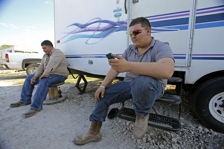 Cesar Garcia uses his cellphone after work as roommate Andres Cadena relaxes alongside their trailer at Lonesome Creek RV Resort near Kenedy, which in the Eagle Ford Shale region. Photo: Tom Reel / San Antonio Express-News