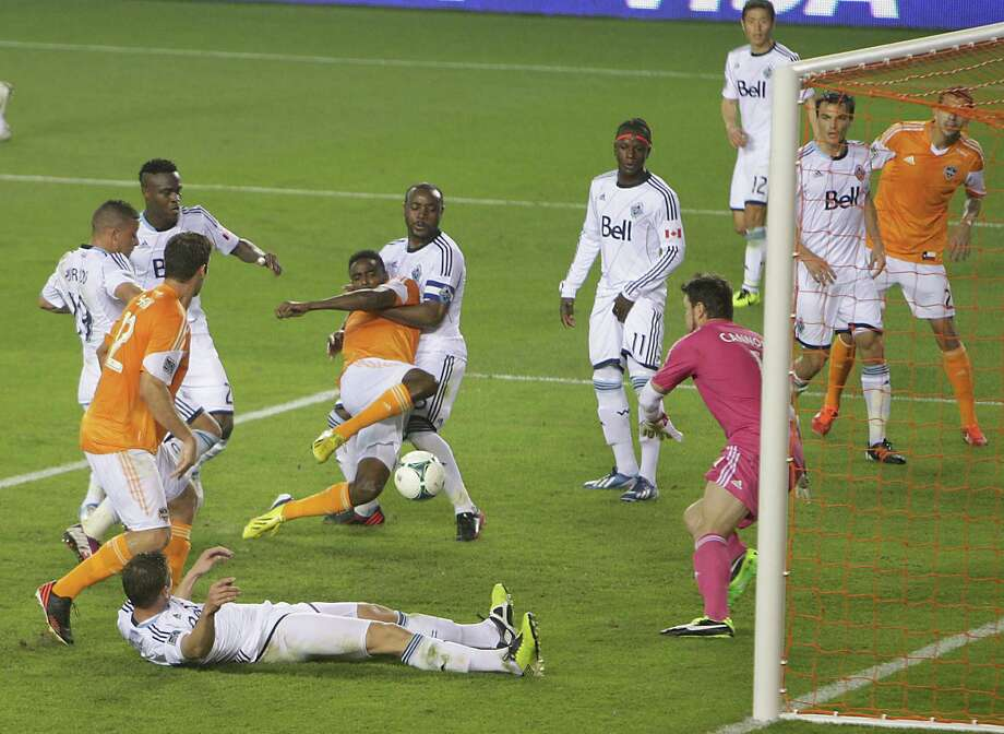 The Dynamo's Warren Creavalle manages to score the winning goal despite being pulled down by the Whitecaps' Nigel Reo-Coker in the penalty area. Photo: James Nielsen, Staff / © 2013 Houston Chronicle