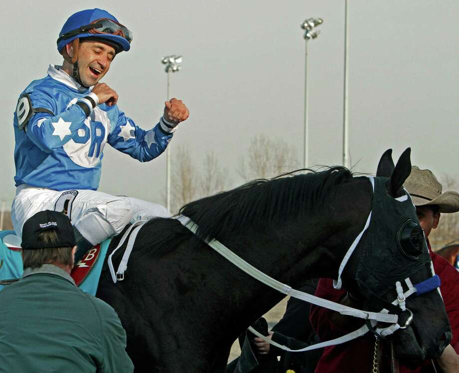 Jockey Joe Bravo celebrates aboard Black Onyx after winning the $550,000 Spiral Stakes horse race at Turfway Park racetrack in Florence, Ky., Saturday, March 23, 2013. (AP Photo/Garry Jones) Photo: Garry Jones