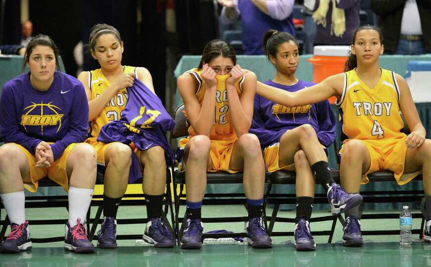 Troy's #12Courtney Avery, center, is comforted by teammate Kiana Patterson, at right, after losing t