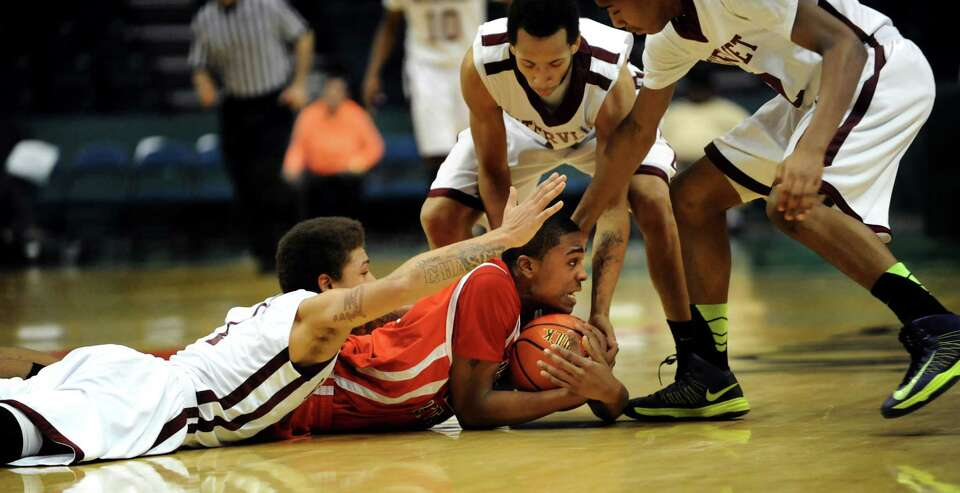 Fannie Lou Hamer's Corey Morgan, center, protects the ball from Watervliet's players during their Cl