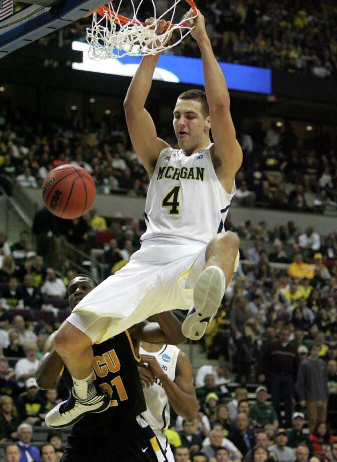 Michigan forward Mitch McGary, a 6-foot-10 freshman, dunks for two of his season-high 21 points in front of VCU guard Treveon Graham in the second half. Photo: Kirthmon F. Dozier / McClatchy-Tribune News Service
