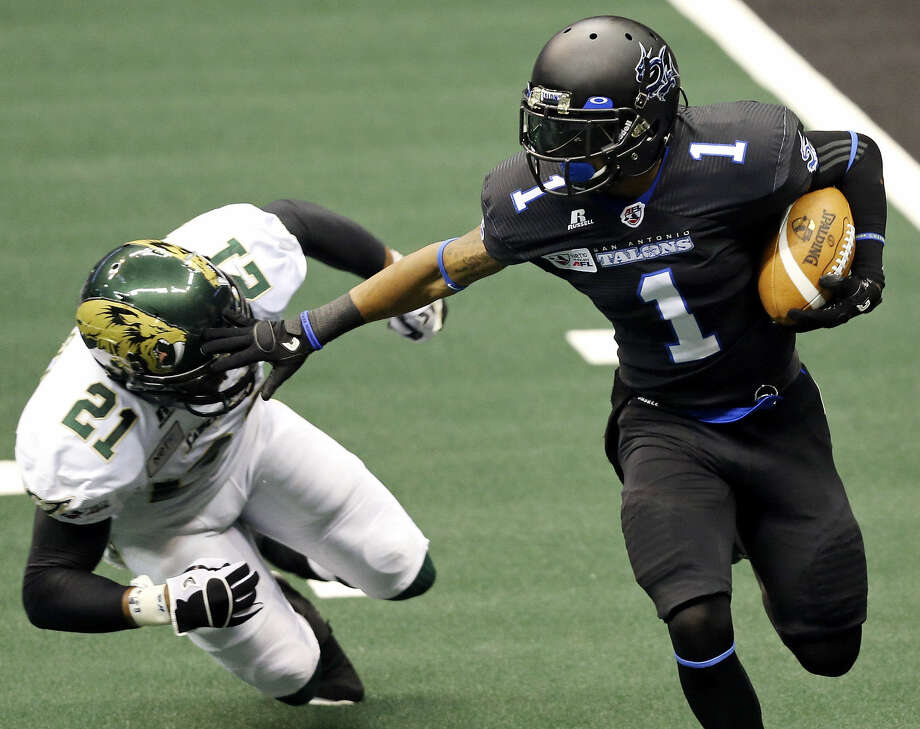 The Talons' Dwayne Eley Jr. looks for room around the San Jose SaberCats' Jamarko Simmons during first-half action at the Alamodome. San Jose defeated the Talons in the season opener before 8,161 fans. Photo: Edward A. Ornelas / San Antonio Express-News