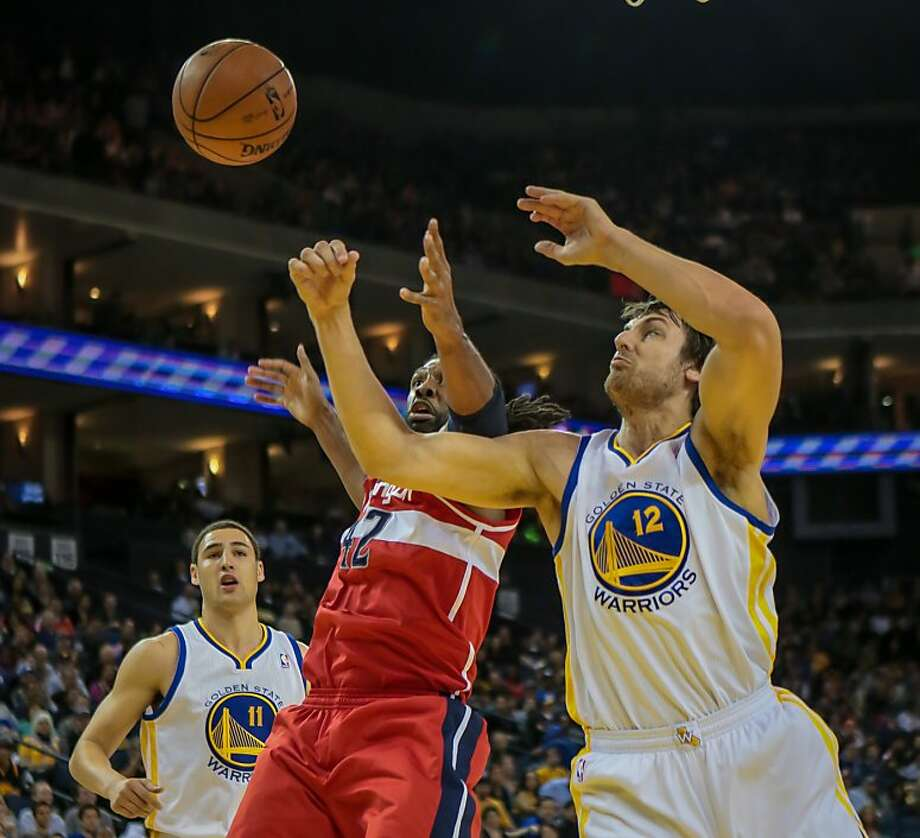 Andrew Bogut (right) tries to fend off Nene for a rebound in the first quarter, when the Warriors jumped to a 15-point lead. Bogut finished with 10 points. Photo: John Storey, Associated Press