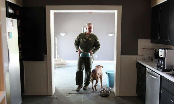 Air Force Reservist Major Shad Magann puts out food for his dogs at his home in Warrensburg, Missouri before heading to work on Thursday, March 7, 2013. Magann was  an officer in charge of two close air support teams assigned to the 3-69th Armored Battalion during the Iraq Invasion in March 2003. Magann is now a reservist pilot at Whiteman Air Force Base. He is currently looking for a civilian commercial pilot job. Photo: Kin Man Hui, San Antonio Express-News / © 2012 San Antonio Express-News