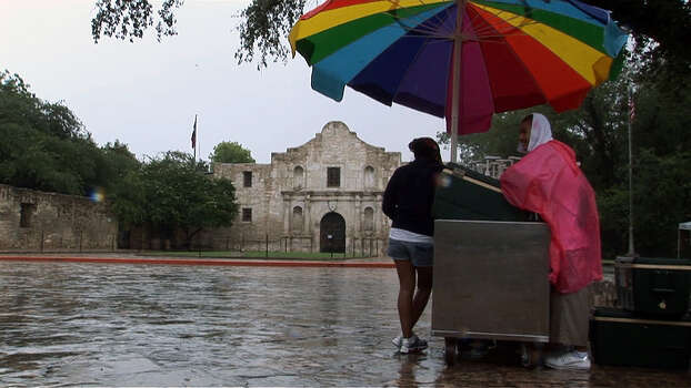 A raspas vendor at the Alamo tries to stay dry under his stand's umbrella while the usual throngs of tourists huddle under awnings across the street, waiting for a thunderstorm to pass through downtown on Tuesday, August 19, 2008. ANGELA GRANT/agrant@express-news.net Photo: ANGELA GRANT, SAN ANTONIO EXPRESS-NEWS / agrant@express-news.net