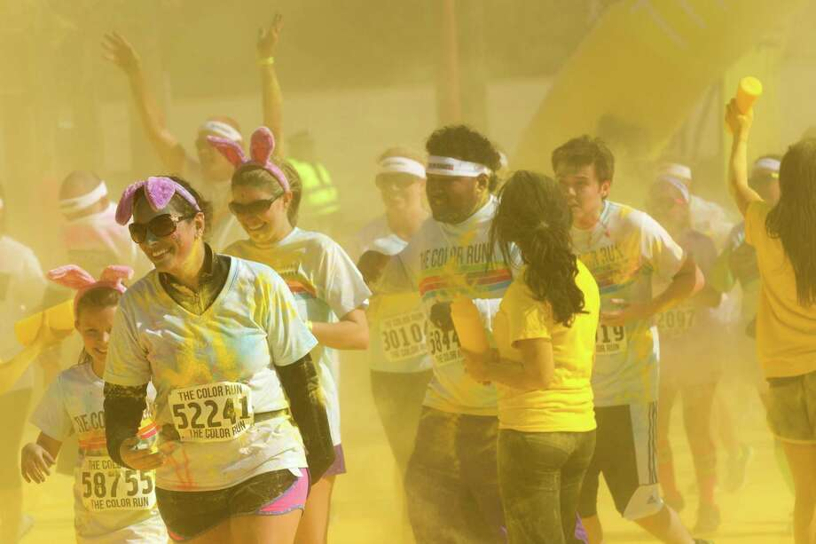 Runners pass through the yellow zone during Color Run Houston 5K run Sunday, March 24, 2013, in Houston. Proceeds from the event benefit Expedition Balance, an organization that helps combat veterans suffering from Post Traumatic Stress Disorder. Photo: Brett Coomer, Houston Chronicle / © 2013 Houston Chronicle
