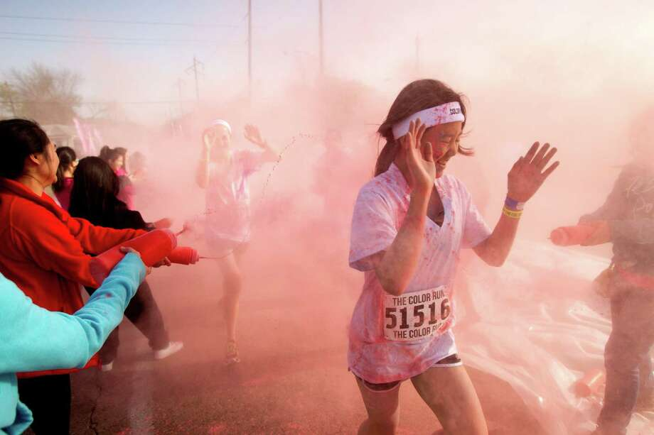 Runners are sprayed with colored cornstarch in the pink zone during Color Run Houston 5K run Sunday, March 24, 2013, in Houston. Proceeds from the event benefit Expedition Balance, an organization that helps combat veterans suffering from Post Traumatic Stress Disorder. Photo: Brett Coomer, Houston Chronicle / © 2013 Houston Chronicle