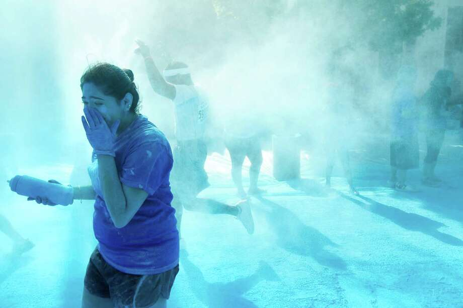 Runners pass through the blue zone during Color Run Houston 5K run Sunday, March 24, 2013, in Houston. Proceeds from the event benefit Expedition Balance, an organization that helps combat veterans suffering from Post Traumatic Stress Disorder. Photo: Brett Coomer, Houston Chronicle / © 2013 Houston Chronicle
