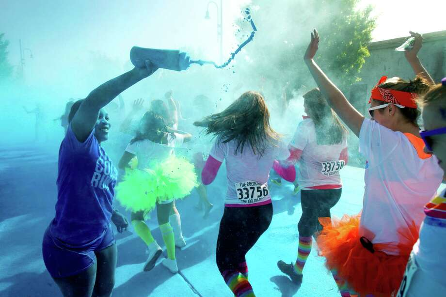 Yennifer Herrera, left, sprays blue cornstarch on runners pass through the blue zone during Color Run Houston 5K run Sunday, March 24, 2013, in Houston. Proceeds from the event benefit Expedition Balance, an organization that helps combat veterans suffering from Post Traumatic Stress Disorder. Photo: Brett Coomer, Houston Chronicle / © 2013 Houston Chronicle
