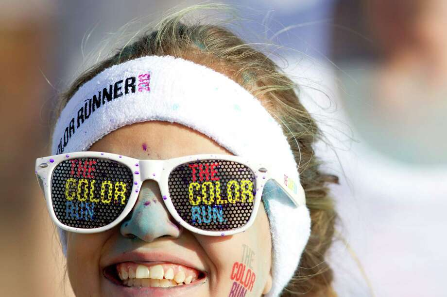 Runners participating in the Color Run Houston 5K run adorn logos from the event Sunday, March 24, 2013, in Houston. Proceeds from the event benefit Expedition Balance, an organization that helps combat veterans suffering from Post Traumatic Stress Disorder. Photo: Brett Coomer, Houston Chronicle / © 2013 Houston Chronicle