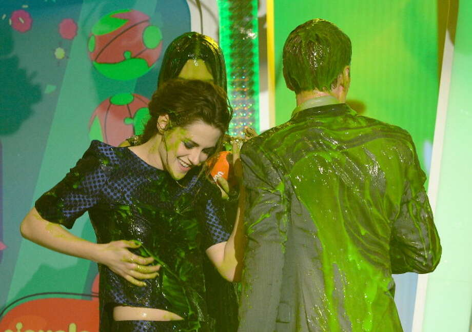 "LOS ANGELES, CA - MARCH 23:  Actress Kristen Stewart (L), winner of Favorite Movie Actress for ""The Twilight Saga: Breaking Dawn ñ Part 2,"" and presenters Sandra Bullock and Neil Patrick Harris are seen onstage after getting slimed during Nickelodeon's 26th Annual Kids' Choice Awards at USC Galen Center on March 23, 2013 in Los Angeles, California.  (Photo by Kevork Djansezian/Getty Images for KCA) Photo: Kevork Djansezian, Getty Images For KCA / Getty Images"