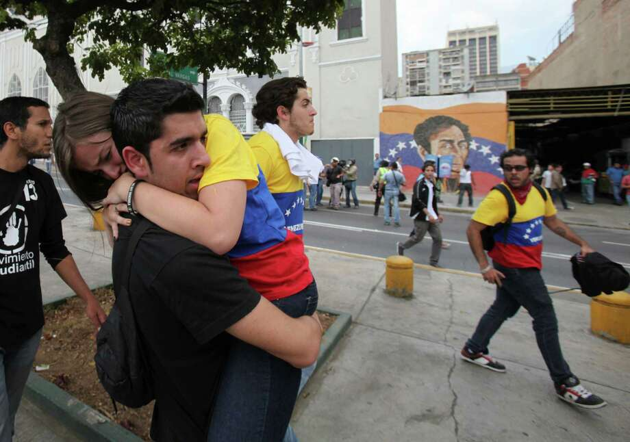 An opposition student protester carries and fellow protester after police launched tear gas during their march toward the electoral commission in downtown Caracas, Venezuela, Thursday, March 21, 2013.  Student protesters marching to protest against what they perceive as bias by Venezuela's electoral council clashed on Thursday with supporters of the late President Hugo Chavez.  Police attempted to separate the rival groups, but scuffles soon broke out, prompting security forces to fire tear gas canisters and shoot plastic bullets at the Chavistas. Photo: AP