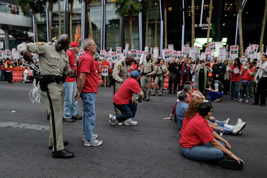 A Las Vegas Metropolitan Police officer arrests a protestor during a civil disobedience demonstration by Culinary Union workers outside the Cosmopolitan Hotel-Casino, Wednesday, March 20, 2013, in Las Vegas. Nearly 98 protestors were arrested during the demonstration in which they sat on and blocked traffic along Las Vegas Boulevard. Workers have been in contract talks with Cosmopolitan Las Vegas owner Deutsche Bank for two years. Photo: AP