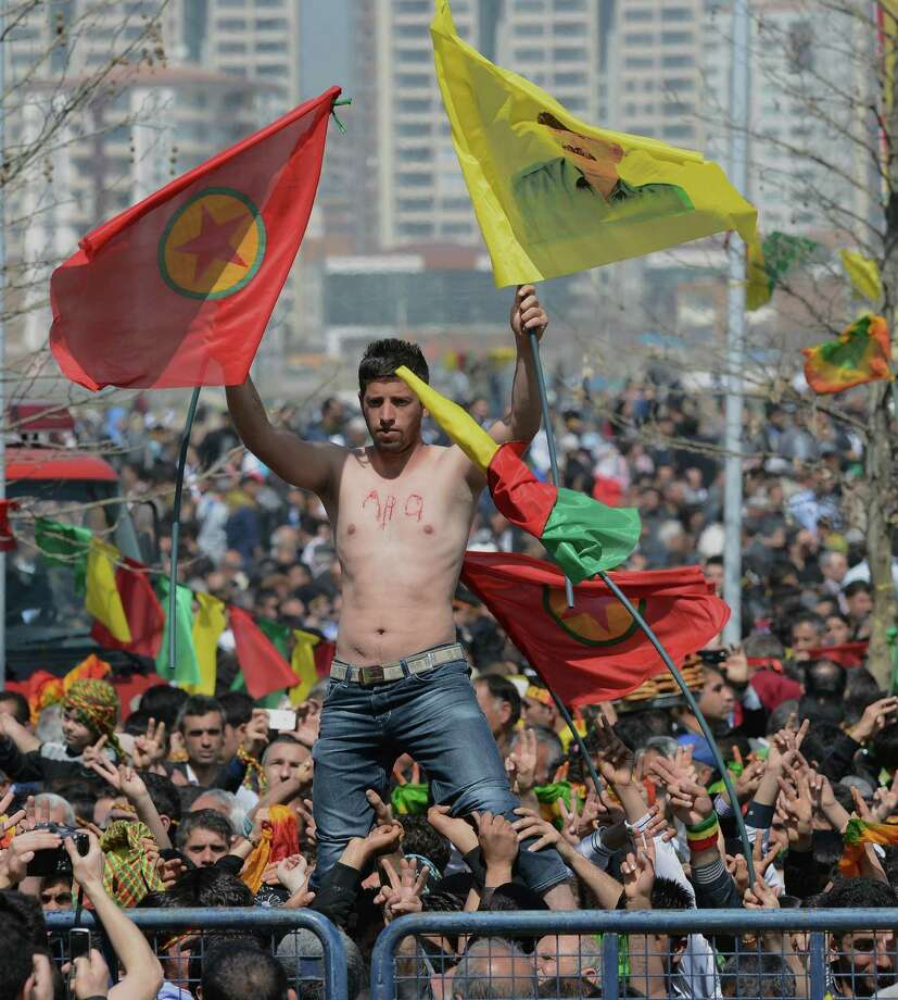 A man stands high above other demonstrators waving PKK flag and an image of jailed Kurdish rebel leader Abdullah Ocalan, in southeastern Turkish city of Diyarbakir, Turkey, Thursday, March 21, 2013, as Ocalan called Thursday for an immediate cease-fire and for thousands of his fighters to withdraw from Turkish territory, a major step toward ending the fighting for self-rule for Kurds in southeastern Turkey, one of the world's bloodiest insurgencies lasting nearly 30-years and costing tens of thousands of lives. Photo: AP