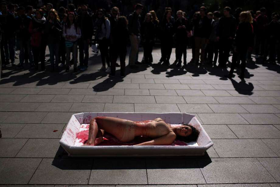 "An animal rights activist from the group 'Animal Equality' lies in a tray representing meat packaging during a protest to celebrate the ""Day Without Meat"" event in Barcelona, Spain, Wednesday, March 20, 2013. Photo: AP"
