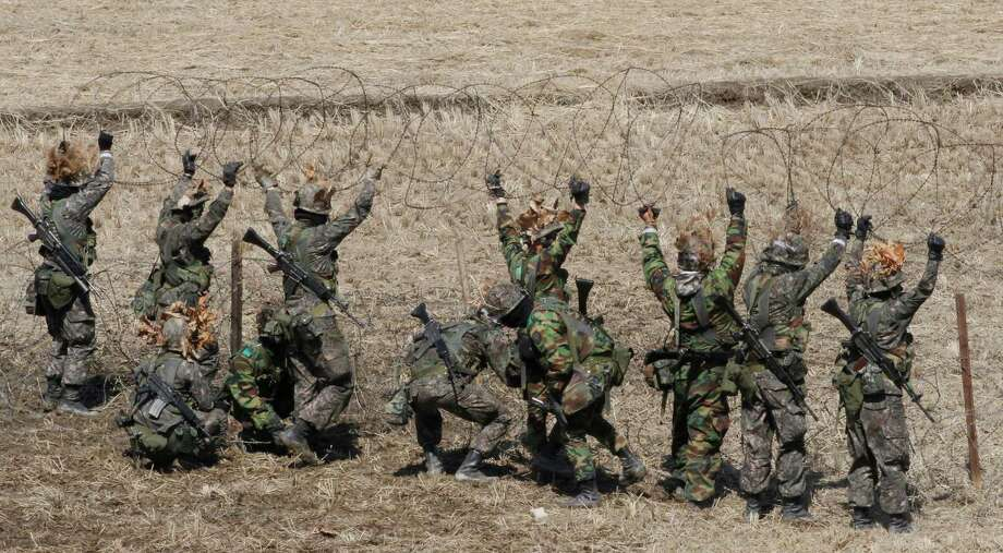 South Korean Army soldiers set up barbed wire fence during an exercise against possible attacks by North Korea near the border village of Panmunjom in Paju, South Korea,Thursday, March 21, 2013. North Korea has threatened revenge for the sanctions and for ongoing U.S.-South Korean military drills, which the allies describe as routine but which Pyongyang says are rehearsals for invasion. Photo: AP