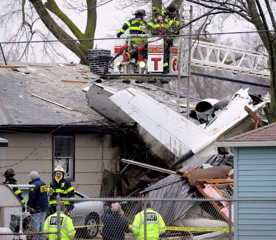 South Bend firefighters work a home, Monday, March 18, 2013, in South Bend, Ind., where a plane crashed Sunday. The plane damaged homes, as well as caused injuries, including at least two fatalities. Photo: AP