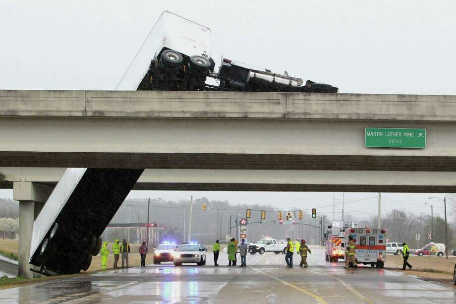 Emergency personal stay dry under one bridge in Tupelo, Miss., as an overturned tractor trailer hangs off the adjacent  bridge after it was blown off by high winds that hit North Mississippi Monday, March 18, 2012. Photo: AP