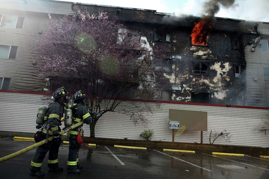 Firefighters battle a four-story apartment fire on Friday, March 22, 2013 in Seattle's Pinehurst neighborhood. The fire damaged six units of the building and was apparently started by a burning motorcycle in the parking garage. (AP Photo/seattlepi.com, Joshua Trujillo)  Photo: AP