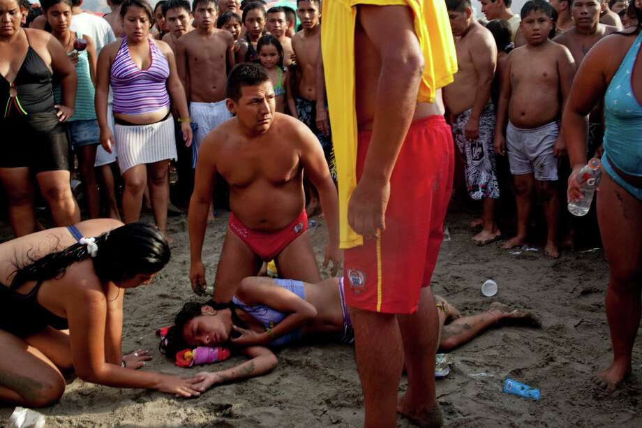 """In this March 3, 2013 photo, life guards attend Belen Godinez on""""Agua Dulce"""" beach after she was saved from drowning in the ocean in Lima, Peru. While Lima's elite spends its summer weekends in gate beach enclaves south of the Peruvian capital, the working class jams by the thousands on a single municipal beach of grayish-brown sands and gentle waves. The only barrier to entry to """"Agua Dulce"""" beach is two dollars, the price of bus fare to get there and home. Photo: AP"""