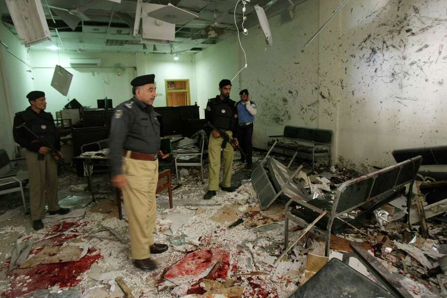 Pakistani police officers examine the site of suicide bombing inside a court room in Peshawar, Pakistan, Monday, March 18, 2013. A pair of suicide bombers attacked a court complex in the northwestern Pakistani city of Peshawar on Monday, killing at least three people and wounding over two dozen, police said. Photo: AP