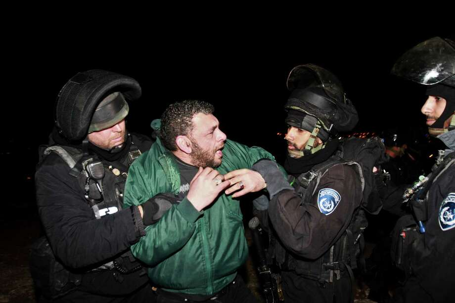 Israeli border policemen evict a Palestinian activist from an area known as E1 near Jerusalem, Sunday, March 24, 2013. Palestinian activists erected tents in the E1 area to protest Israeli plans for a new settlement in the area. Photo: AP