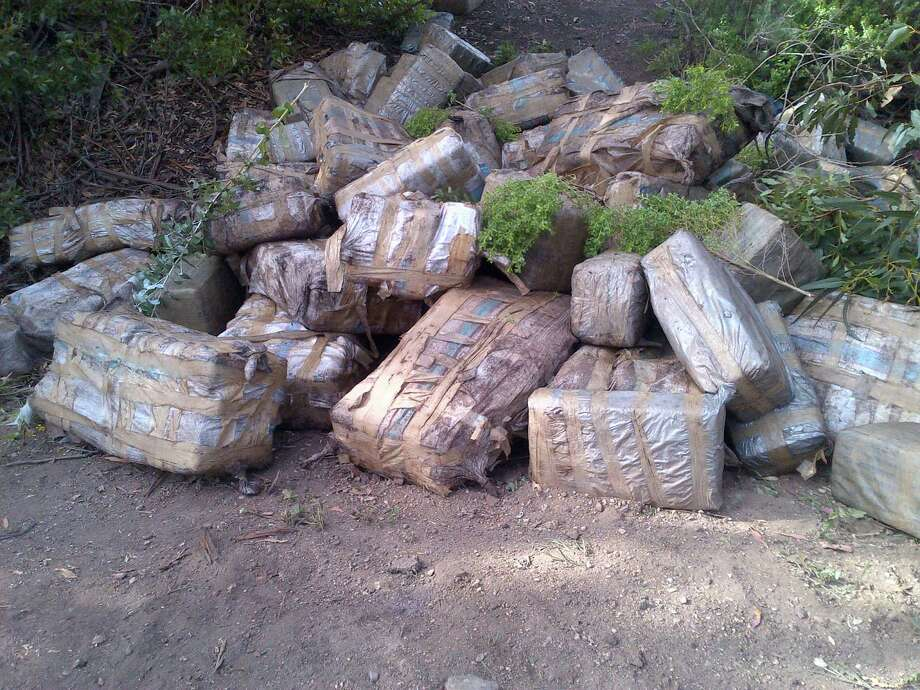 This photo provided by the Santa Barbara County Sheriff's Office shows an estimated $4 million worth of marijuana that was found Sunday, March 17, 2013 at Arroyo Camada beach in Santa Barbara County, Calif., next to a panga boat. There was an estimated 2,000 pounds of pot wrapped in plastic bags on the beach. The boat was apparently abandoned and had at least 20 fuel containers on board. Panga boats are often used for smuggling people or drugs into the United States from Mexico. Photo: AP