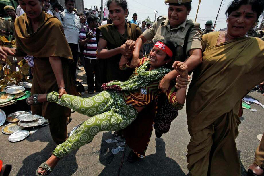 "Indian policewomen detain an activist participating in ""sadak bandh,"" or road strike, on a highway on the outskirts of Hyderabad, India, Thursday, March 21, 2013. The protesters demanded that a new state of Telangana be carved from the existing Andhra Pradesh state. Photo: AP"