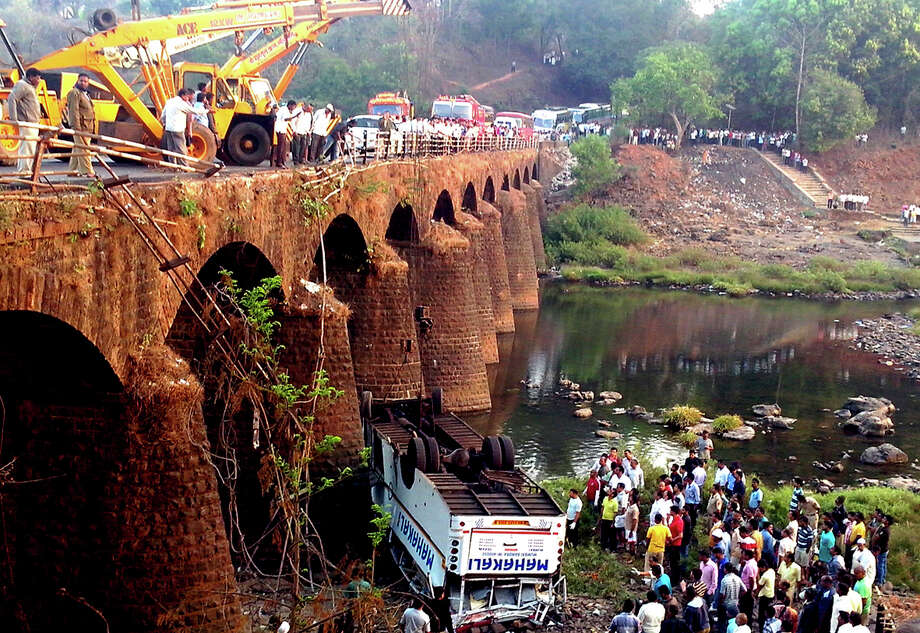 Rescuers and others gather at the site of a bus accident in Ratnagiri district, in the western Indian state of Maharashtra, Tuesday, March 19, 2013. The bus packed with passengers crashed through a guard rail and fell off a bridge in western India early Tuesday, killing at least 37 people and injuring another 15, police said. Photo: AP