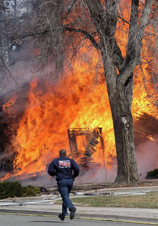 A Grand Junction fire department responder races up Seventh Street past a wall of flames from one of two homes that burned following an explosion Wednesday, March 19, 2013 in Grand Junction, Colo. A strong odor of natural gas was reported in the area before the explosion. Photo: AP
