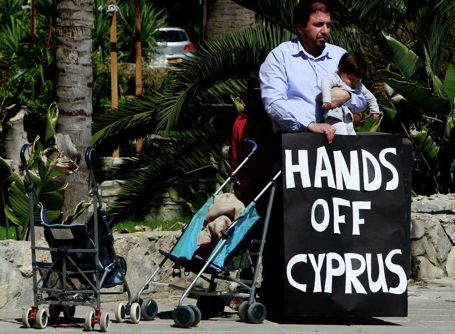 A protestor with his child hold a banner  outside of parliament during a crucial meeting in capital Nicosia, Cyprus, Monday, March 18, 2013. Cyprus' president is briefing lawmakers ahead of a crucial parliamentary vote on a controversial levy on bank deposits that the cash-strapped country's creditors have demanded in exchange for a euro10 billion (US$13 billion) rescue package. Photo: AP