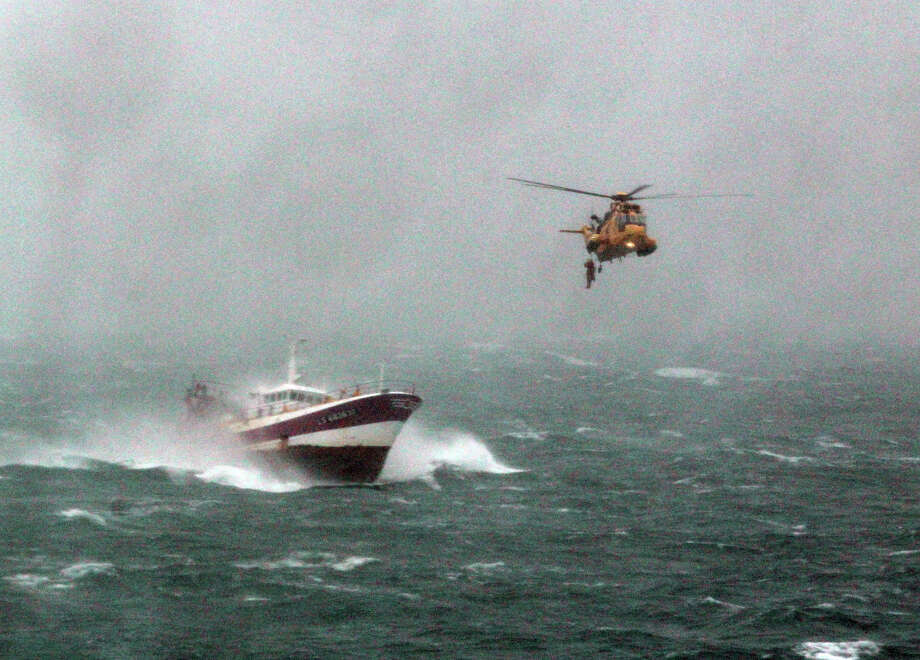 In this image made available by Britain's Royal Navy Friday March 22 2013, RAF Winchwoman Sergeant Rachel Robinson makes her final, successful attempt to transfer from a Sea King helicopter to the deck of the French fishing vessel ALF to rescue a seriously-injured crewman  in atrocious weather in the Irish Sea, 50 miles west of the  coast of Wales on Thursday 21 March. The ALF was pitching and rolling violently, climbing and descending vertically 40 feet with each swell and rolling violently in a 35 knot wind. Photo: AP