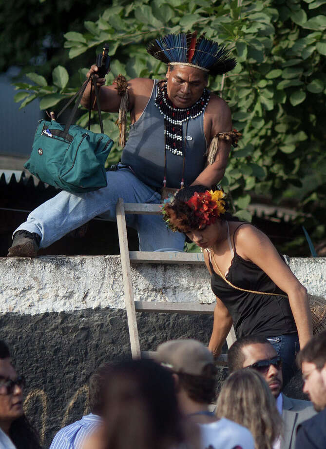 An Indigenous man and woman leave the old Indian Museum as they are evicted from the complex in Rio de Janeiro, Friday, March 22, 2013. Police in riot gear invaded an old Indian museum complex Friday and pulled out a few dozen other indigenous people who for months resisted eviction from the building, which will be razed as part of World Cup preparations next to the legendary Maracana football stadium. Photo: AP