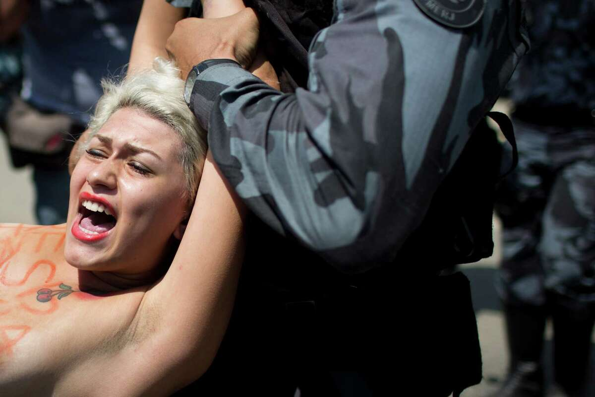 A FEMEN activist is carried away by police while protesting the eviction of indigenous people being from the old Indian Museum in Rio de Janeiro, Friday. Police in riot gear invaded an old Indian museum complex Friday and pulled out a few dozen indigenous people who for months resisted eviction from the building, which will be razed as part of World Cup preparations next to the legendary Maracana football stadium.