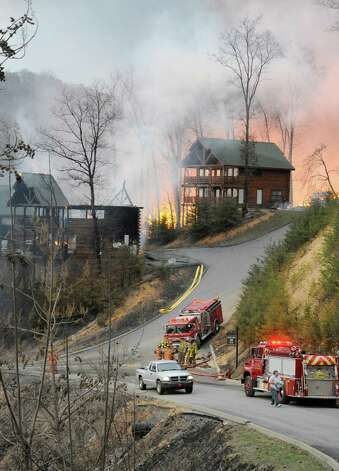Firefighters set a boundary as cabins burn on Black Bear Cub Way in Sevier County, Tenn Sunday March 17, 2013. As of 8:00 p.m. there was 32 cabins reported burned with 40 more in danger as shifting winds started breaking contain lines. Photo: AP