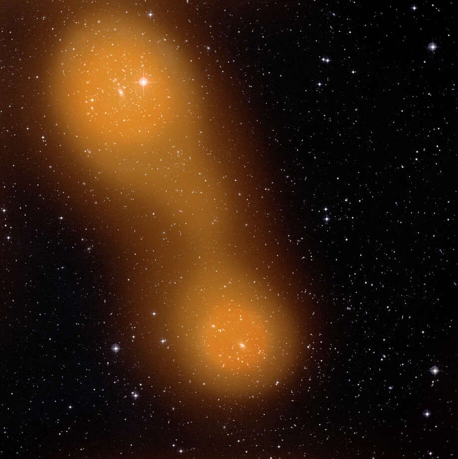 This image made available by NASA on Nov. 21, 2012 shows a bridge of hot gas that connects galaxy clusters Abell 399, lower center, and Abell 401, top left, discovered by the European Space Agency's Planck space probe. The galaxy pair is located about a billion light-years from Earth, and the gas bridge extends approximately 10 million light-years between them. The image shows the two galaxy clusters at optical wavelengths with ground-based telescopes and through the Sunyaev-Zel'dovich effect (in orange) with the Planck satellite. Photo: AP