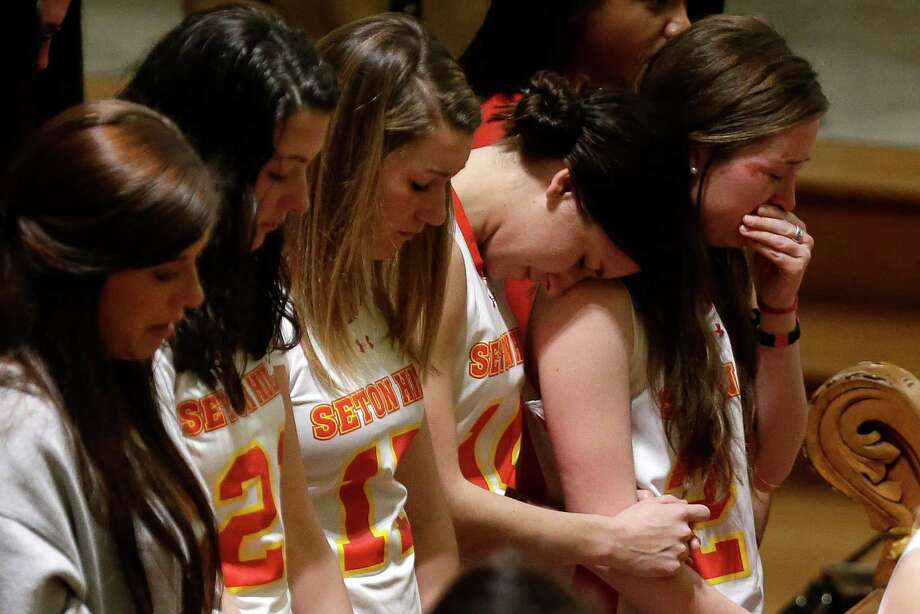 Members of the Seton Hill University's women's lacrosse team attend a memorial mass in St. Joseph Chapel on  the school's  Greensburg, Pa., campus Sunday, March 17, 2013. Women's lacrosse coach Kristina Quigley and the tour bus driver were killed when their tour bus carrying three coaches and members of the lacrosse team when the bus crashed at about 9 a.m., turnpike spokeswoman Renee Colborn said. It's not clear what caused the crash, but state police were investigating, said Megan Silverstram of the Cumberland County public safety department. Photo: AP