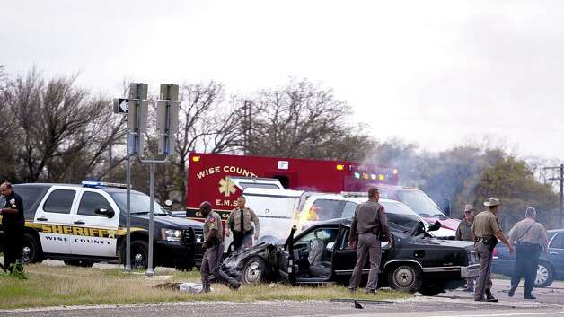 Emergency personnel are on the scene of a crash and shootout with police involving the driver of a black Cadillac with Colorado plates in Decatur, Texas, Thursday, March 21, 2013. The driver led police on a gunfire-filled chase through rural Montague County, crashed his car into a truck in Decatur, opened fire on authorities and was shot, officials said.  Texas authorities are checking whether the Cadillac is the same car spotted near the home of Colorado prisons chief Tom Clements, who was shot and killed when he answered the door Tuesday night. (AP Photo/Wise County Messenger, Jimmy Alford)  Photo: AP