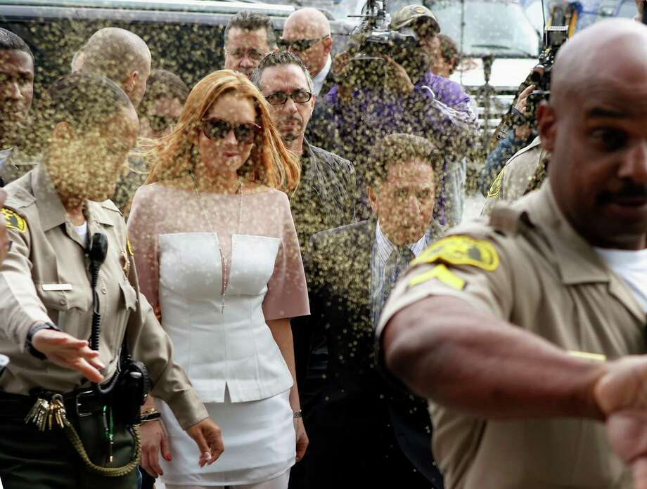 Actress Lindsay Lohan is showered with gold glitter, second left, as she arrives with her attorney Mark Heller, after attending a trial Monday, March 18, 2013, at  Los Angeles Superior court. Lohan is charged with three misdemeanor counts stemming from a crash on Pacific Coast Highway. She is charged with willfully resisting, obstructing or delaying an officer, providing false information to an officer and reckless driving. She is also accused of violating her probation in a misdemeanor jewelry theft case. Photo: AP