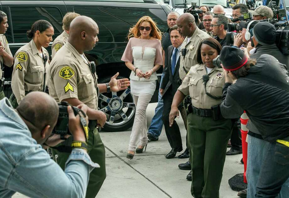 Actress Lindsay Lohan walks with her attorney Mark Heller, at Los Angeles Superior court on Monday, March 18, 2013. Lohan is charged with three misdemeanor counts stemming from a crash on Pacific Coast Highway. She is charged with willfully resisting, obstructing or delaying an officer, providing false information to an officer and reckless driving. She is also accused of violating her probation in a misdemeanor jewelry theft case. Photo: AP